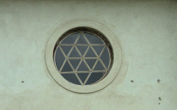 A stained-glass oculus displaying Star of David emblem over the main entrance at the synagogue in Orla
