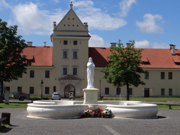 The Zhovkva Castle, in the 17th century a royal residence of Polish king Jan III Sobieski, a fountain with the statue of Virgin Mary in the foreground